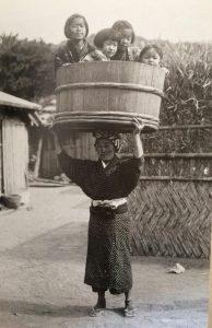 子どもを乗せた桶を頭上で支える女性