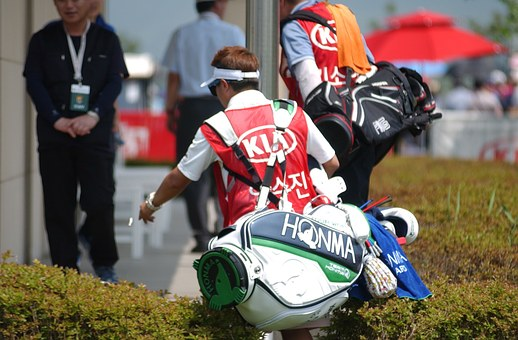 ゴルフバッグ担ぐ男性